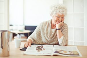 Older woman reading the newspaper at the dinner table
